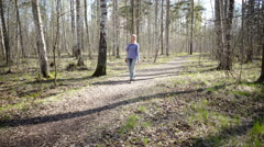 The happy woman goes on a footpath in park in  early spring Stock Footage