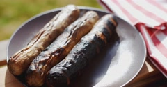 Three charred sausages outside Stock Footage