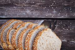 A sliced whole grain bread with sesame seeds. - stock photo