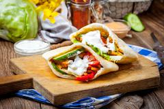 Fried chicken meat with vegetables in pita bread Stock Photos