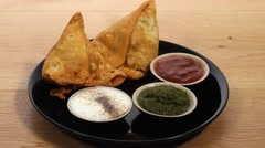 Track shot of a black plate of Samosa and chutney served Stock Footage