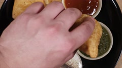 Top-shot track-in close-up of a hand grabbing a Samosa from a plate Stock Footage
