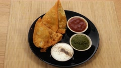 Tracking in to a plate of Samosa and chutney served Stock Footage