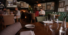 4K Young group chatting in restaurant with table settings ready in foreground Stock Footage