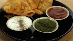 Close-up track out to a plate of Samosa served with chutney Stock Footage
