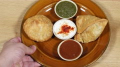 Samosa and kachori being served with condiments, top-shot Stock Footage