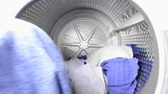 Man putting laundry in tumble dryer - stock footage