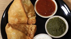 Top-shot track-in close-up of a plate of Samosa served with condiments Stock Footage