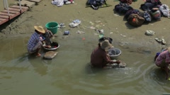 Local people washing clothes in river, Burma - stock footage