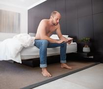 Handsome young man using a digital tablet in bedroom Stock Photos