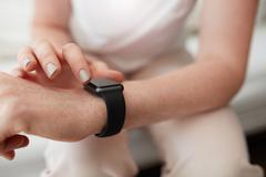 Woman checking time on her smart watch - stock photo