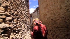 Rear view of local woman walking through alleys of Mustang, Nepal Stock Footage