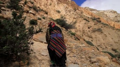 Rear view of a local woman with a stick climbing the hill in Mustang, Nepal Stock Footage