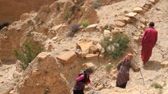 Local man and women climbing up the mountain in Mustang, Nepal - stock footage