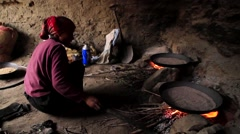 Local woman heating the food grains on fire wood stove, Mustang, Nepal - stock footage