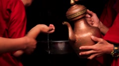 Young monks receiving holy water while entering the monastery Stock Footage