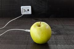 Green apple connected to an ethernet cable - stock photo