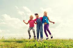 group of happy kids jumping high on green field - stock photo