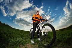 Biker in orange jersey riding on green summer field Stock Photos