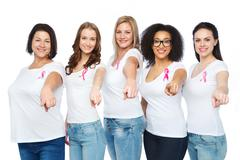 Happy women with breast cancer awareness ribbons Stock Photos