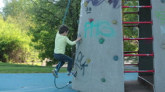 Cute little preschool boy, climbing on a rock wall with rope, little child pl Stock Footage