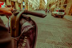 FLORENCE, ITALY - JUNE 12, 2015: Bycicle handlebars with one hand ridding close Stock Photos