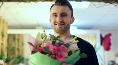 Young handsome guy is going to give flowers to girl. Stock Footage