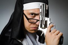 Man dressed as nun with handgun Kuvituskuvat