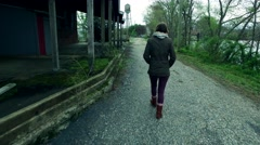 Girl Walking Towards a Water Tower in an Abandoned Factory Stock Footage