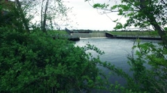 View through the Brush with a Dam and Lake in the Background Stock Footage