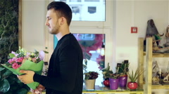 The man is holding bouquet standing in a flower shop. Stock Footage