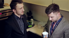 Two men in jackets are talking at the kitchen. - stock footage