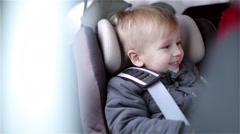 Little happy boy is sitting in the car seat and smiling. Boy likes journey. Stock Footage