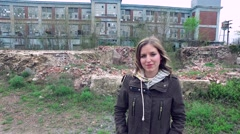 Girl Standing in Front of an Abandoned Factory with her Hair Blowing in the Wind Stock Footage