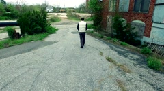 Guy Walking Through the Ruins of an Abandoned Factory Stock Footage