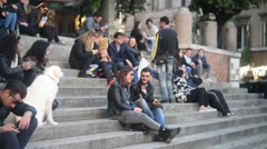 Young People relax and communicate on the steps of the fountain Sisto Rome Italy Stock Footage