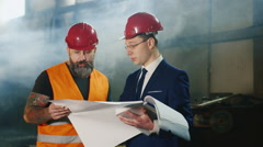 The engineer in a suit and brutal bearded builder together studying blueprints - stock footage