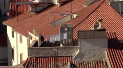 Woman hangs out washing amongst the terracotta tiled rooftops - stock footage