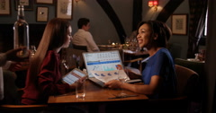 4k, Two businesswoman going over financial statements on a laptop at restaurant Stock Footage