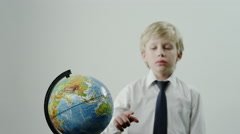Schoolboy rotates the globe Stock Footage
