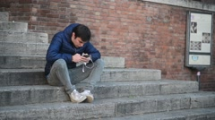 Young Man with mobile sell Phone on the steps of the fountain Sisto Rome Italy Stock Footage