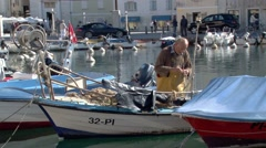 Fisherman tends to nets in the harbour of Piran Stock Footage