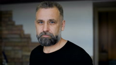 Client parikmazherskoy. Man aged with graying hair. Evaluates haircut beard and - stock footage