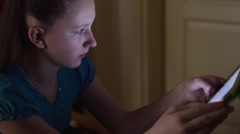Girl play with tablet at evening, dark room  Stock Footage