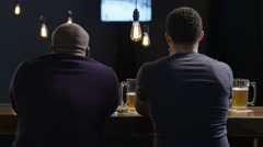 Two guys celebrating victory at a sports bar - stock footage