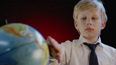 Schoolboy rotates the globe Stock Footage