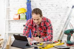 smilling young man using the tablet for DIY - stock photo