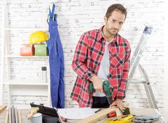 Carpenter drilling hole in plank, in his workshop - stock photo