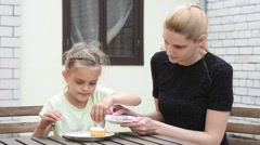 Mom and daughter seven years in the courtyard sitting at the table - stock footage