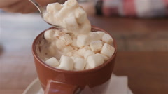 Cocoa with marshmallows.man takes a spoon of cocoa with marshmallows Stock Footage